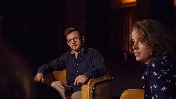 Moderator Dominik Braun und Karina Stützel (Protagonistin) hören Talkgast David Leubner (nicht im Bild) zu.