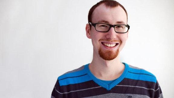 Lachender junger Mann mit Brille