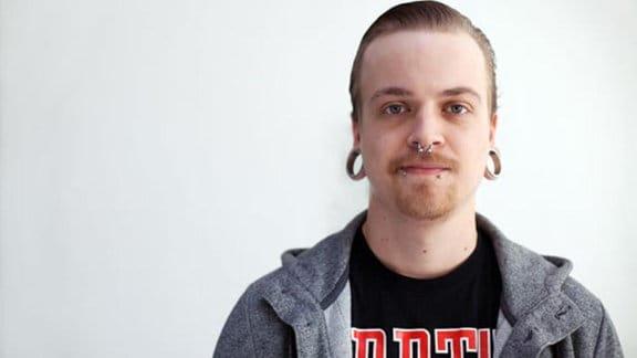 Junger Mann mit Bart und Fleischringen