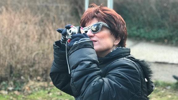 Frau mit kurzen, dunkelroten Haaren und Sonnenbrille fotografiert etwas mit einer Digitalkamera