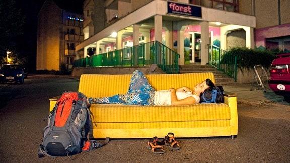 Eine COuchsurferin liegt mitten auf einer Straße auf einer Couch.