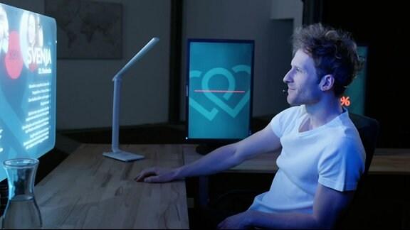 Ein junger Mann sitzt vor einem großen Bildschirm.
