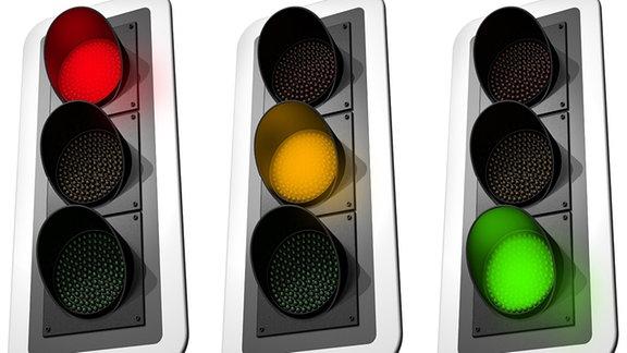 Drei Ampeln zeigen rot, gelb und grün