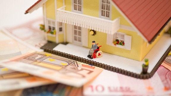 Eine Spielzeugfigur sitzt, im Rollstuhl, im Vorgarten eines Spielzeughauses, dass auf Geldscheinen steht.
