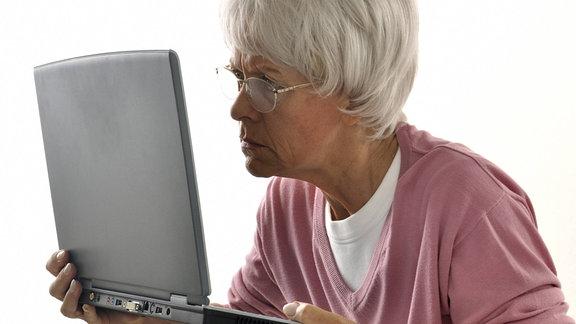 Eine Seniorin hält sich einen Laptop dicht vor die Augen