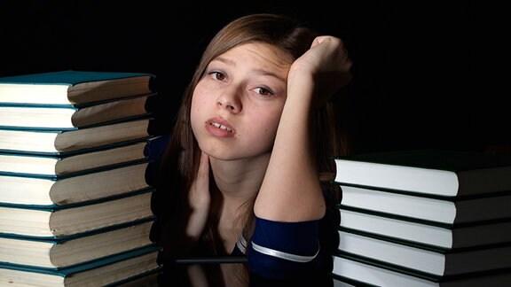 Eine verzweifelt blickende Schülerin sitzt zwischen aufgestapelten Büchern