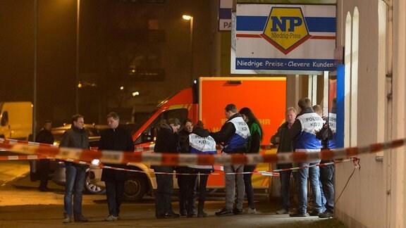 """Es zeigt Polizeibeamte vor einem Supermarkt der Kette """"NiedrigPreis""""."""