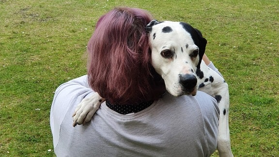 Sue hält ihren Hund im Arm.