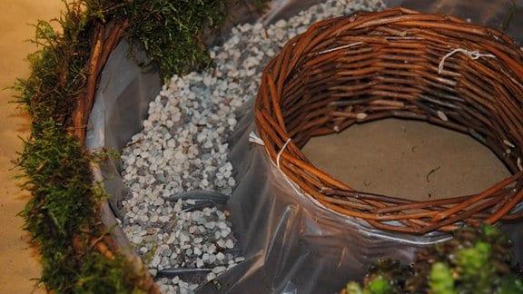 Kieselsteine bedecken den Boden eines Pflanzrings aus Korbgeflecht