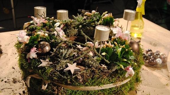 Ein Adventskranz mit lebendigen Pflanzen, Moos, Zweigen und Holzsternen