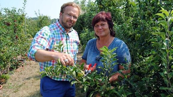 MDR Garten-Moderator Jens Haentzschel steht mit der Obstbau-Expertin Monika Möhler, die eine rote Gartenschere hält, in einer Plantage mit Obstbäumen neben einem Apfelbaum