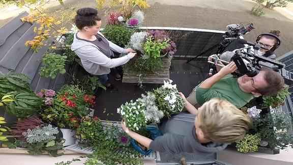 Viele Leute arbeiten auf einem Balkon - Kameraperspektive von oben.