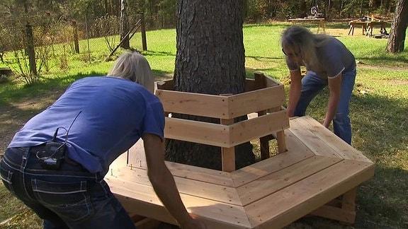 Zwei Männer bauen eine Bank um einen Baumstamm