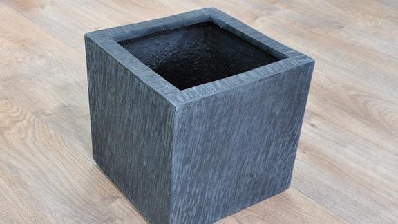 auf dem Fußboden steht ein dunkelgrauer, quadratischer Blumenkübel