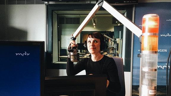 """Carolin Engwert, Autorin des Buches """"Abenteuer Garten"""", sitzt mit Kopfhörern im Radiostudio."""