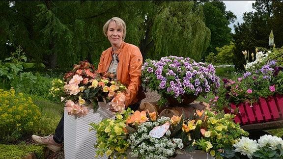 Sonja Dümmen sitzt zwischen vielen Blumentöpfen