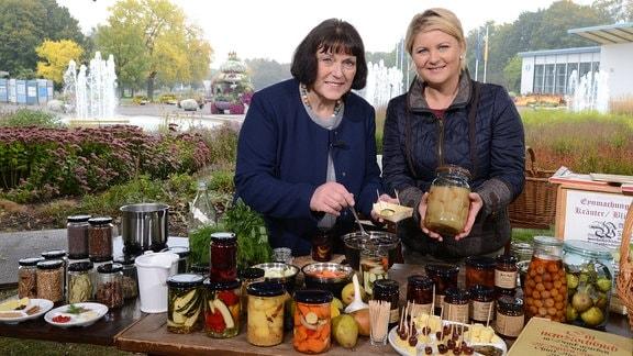 Zwei Frauen stehen hinter einem Tisch auf dem viele Gläser mit eingewecktem Obst und Gemüse stehen.