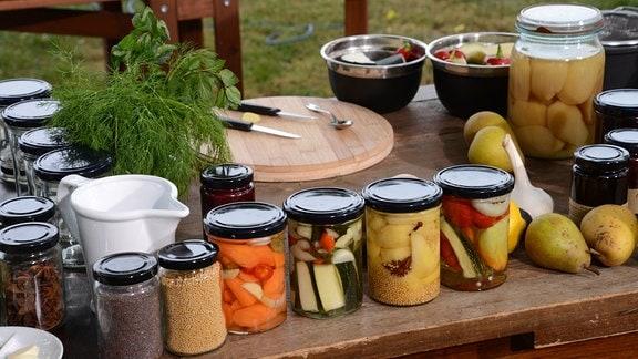 Auf einem Tisch stehen viele Gläser mit eingewecktem Obst und Gemüse.