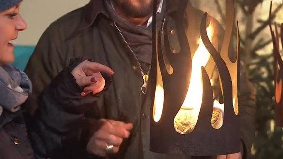 Ein zylinderförmige Fackel aus Cortenstahl in Form von stilisierten aufsteigenden Flammen, in der ein Feuer brennt