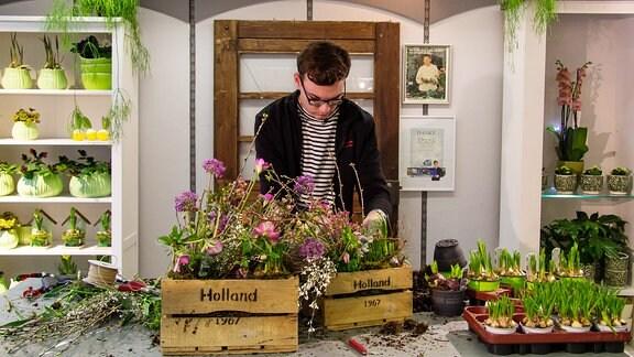 Ein junger Mann lächelt. Hinter ihm stehen Blumen.
