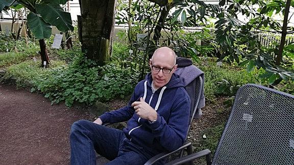 Botaniker Stefan Arndt sitz auf einer Bank in einem Gewächshaus des Botanischen Gartens Jena.