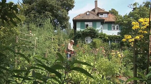 Eine Frau gießt Blumen in einem Garten