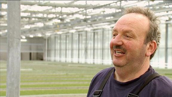 Ein Kressezüchter im Interview in einem industriellen Gewächshaus