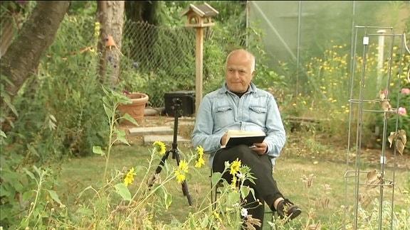 Künstler Assisi sitzt in einem Garten und zeichnet.