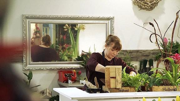 Eine junge Frau arbeitet an einem Blumengesteck