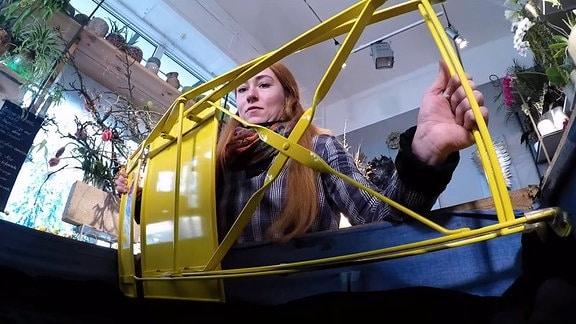 Floristin Annekatrin begutachtet einen gelben Klappstuhl.