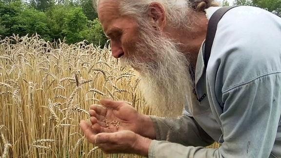 Filmszene - Ein älterer, langbärtiger Mann pusten in seine Hände voll Samen.