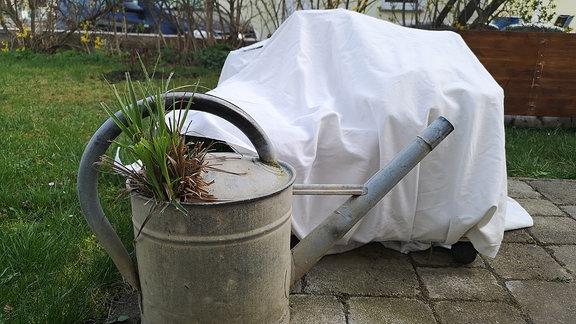 Ein Blumenkübel ist mit einem Laken/ Vlies zugedeckt. Im Vordergrund steht eine Zink-Gießkanne.