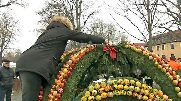 Letzte Handgriffe an der Krone des Osterbrunnens in Langenwetzendorf