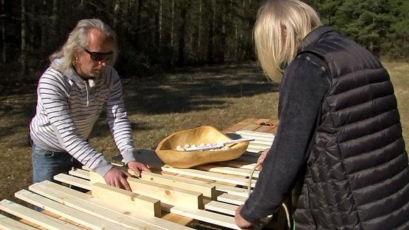 Zwei Männer beim Arbeiten an Holzlatten