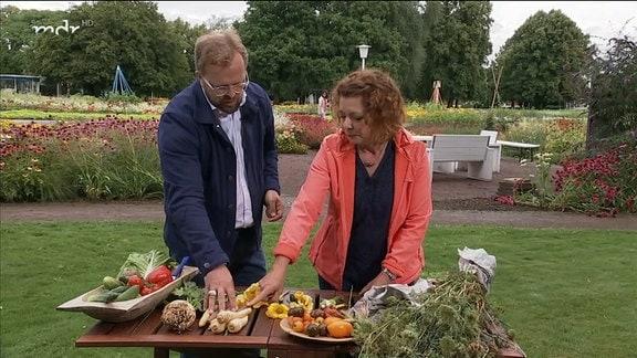 Zwei Menschen begutachten einen Tisch mit Gemüse