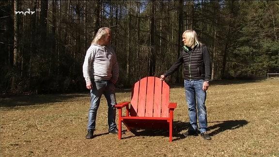 Zwei Männer und ein roter Stuhl.