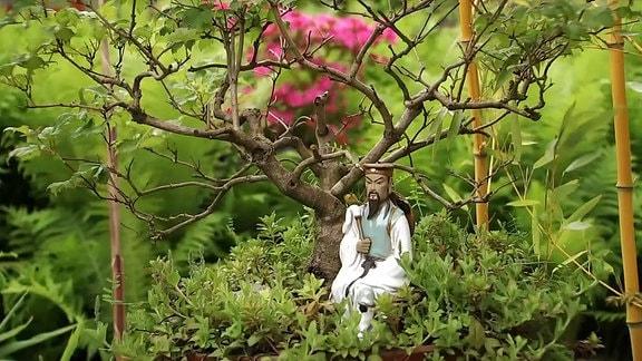 Japanische Figur unter einem Bonsei