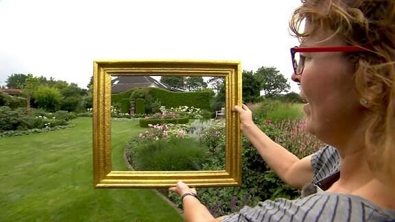 Eine Gartenbesitzerin hält einen Bilderrahmen in einem Garten in die Höhe.
