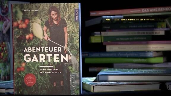 Buch 'Abenteuer Garten - Mein erstes Jahr im Schrebergarten' von Carolin Engwert neben einem Bücherstapel