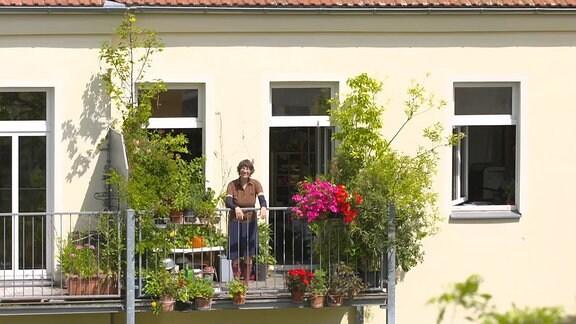 Eine Frau steht auf einem Balkon mit vielen Pflanzen
