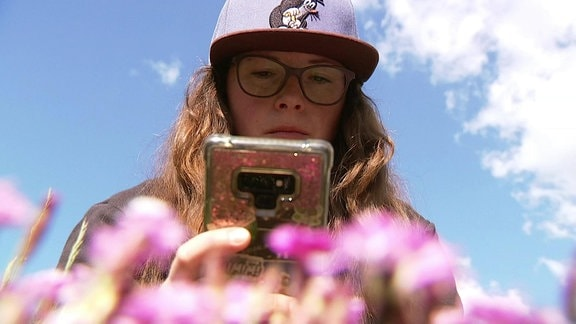 Gärtnerin Melanie Trinks bestimmt Pflanze mit Handy-App