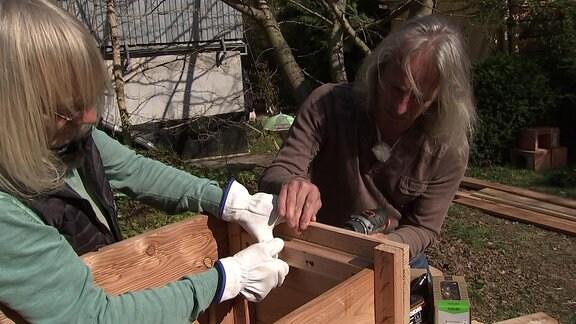 Zwei Männer arbeiten an einer Sitzmöglichkeit für den Garten
