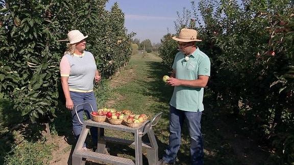 Moderatorin und Gast stehen auf einer Apfelwiese