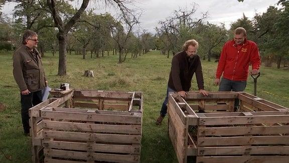 Drei Männer stehen hinter zwei Kompostkisten.