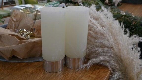 Zwei weiße Stumpenkerzen vor Pampasgräsern auf einem Holztisch.