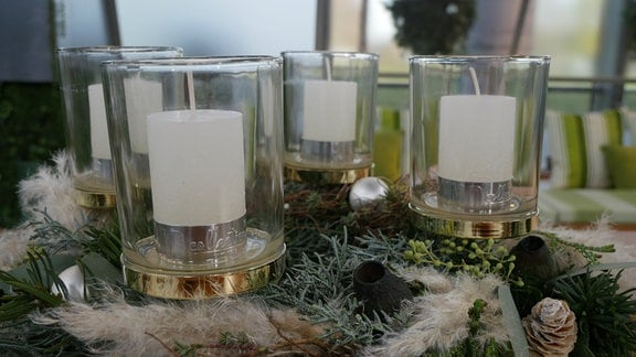 Ein Adventskranz mit Dekor um Kerzengläser drapiert. In den Gläsern stehen weiße Stumpenkerzen.