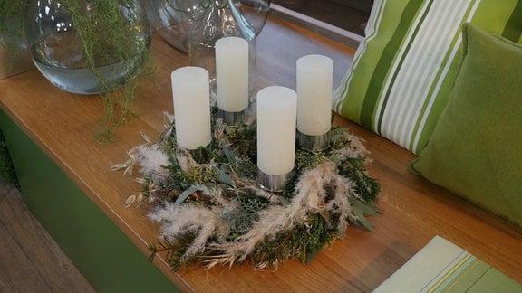 Ein Adventskranz aus Grünschnitt und trockenen Gräsern. Darauf vier große Stumpenkerzen.