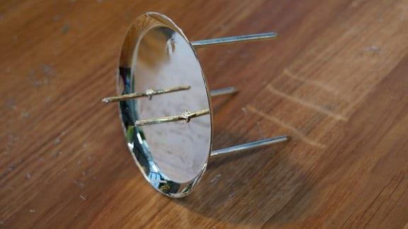 Ein dreibeiniger Kerzenteller für Stumpenkerzen. Aus dem Teller ragen zwei Nadeln hervor.