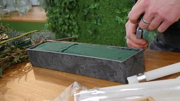 Eine rechteckige Keramikschale randvoll gefüllt mit feuchter Steckmasse.