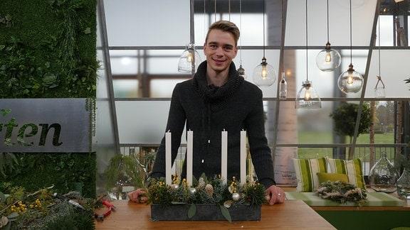 Florist Martin Neumann mit dem fertigen Kerzengesteck im MDR Garten-Studio.
